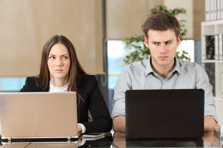 Front view of two angry people using computers