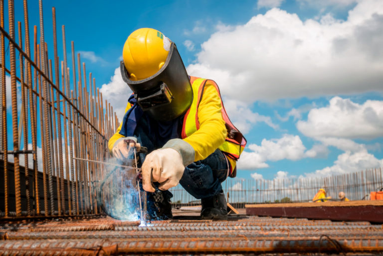 Man welding metal in construction site