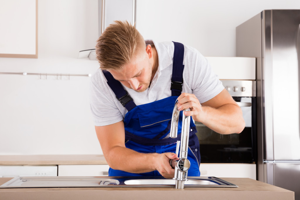 plumber fixing the kitchen faucet