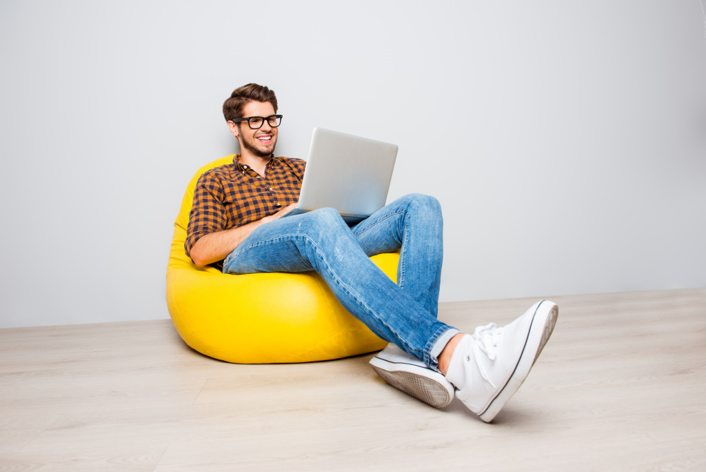 Man using laptop while sitting on yellow chair