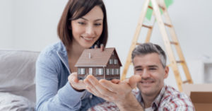 couple holding a house toy