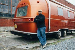 man standing next to an RV