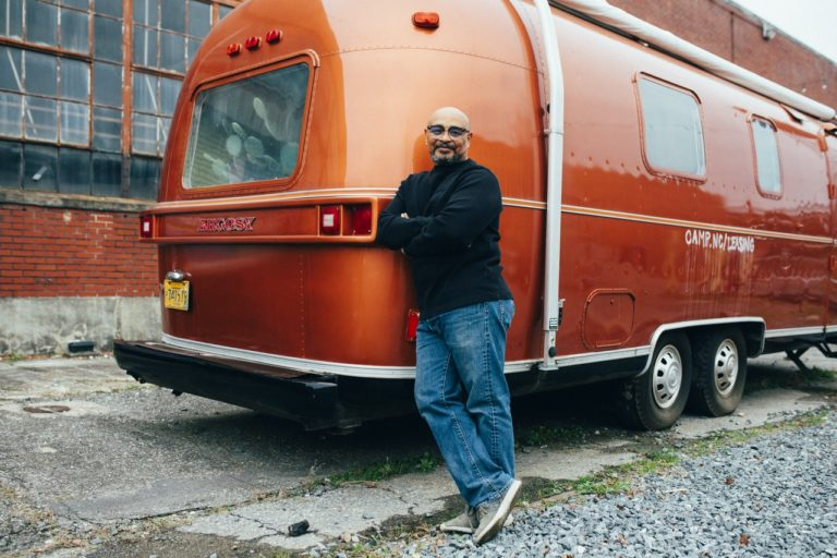 man standing next to an RV