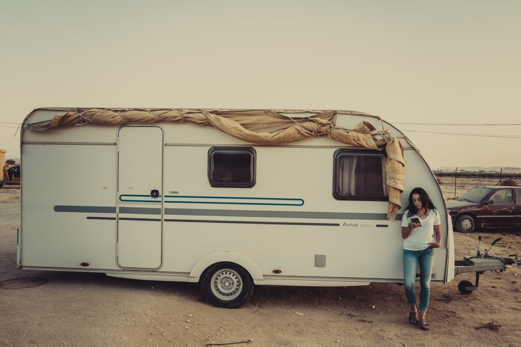 woman standing next to a camper