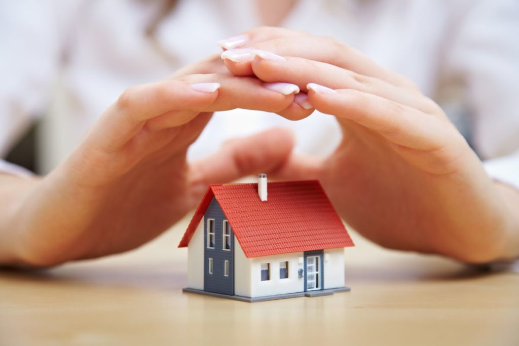 hand hovering over miniature house model